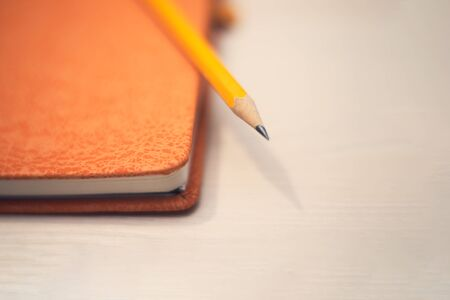 A pencil on the orange day book on the purple background. Concept idea. Space for text. Stock Photo - 138195716