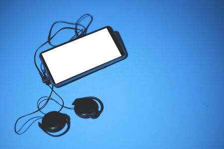 Top view of black mobile phone gadget with round earpieces and white screen for text laying on the blue background.