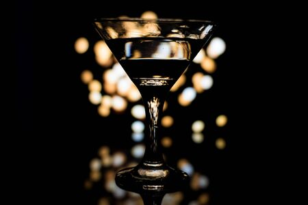 A martini glass with some drink and reflection, on the bright coloured background.