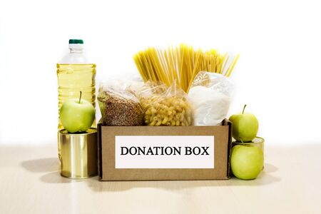 Full donation food box with many products on the white background. Charity concept.