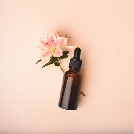 Serum glass bottle with pipette and beautiful flower on the beige pink background. Natural Organic Spa Cosmetic concept. Front view.