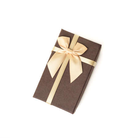 Brown craft gift box with satin beige ribbon bow isolated on white background. Stockfoto