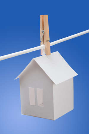 Paper house with clothespin, hanging from rope on blue background. real estate concept photo