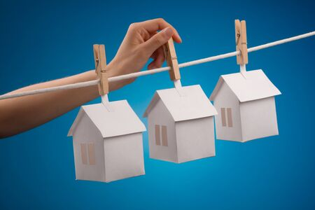 Paper house with clothespin, hanging from rope on blue background  Selective focus  photo