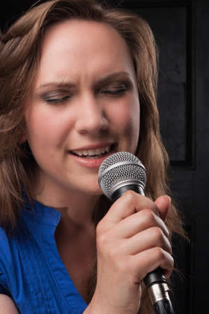Girl singing to the microphone in a studio photo