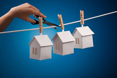 Paper house with clothespin, hanging from rope on blue background  Selective focus Stock Photo - 15039635