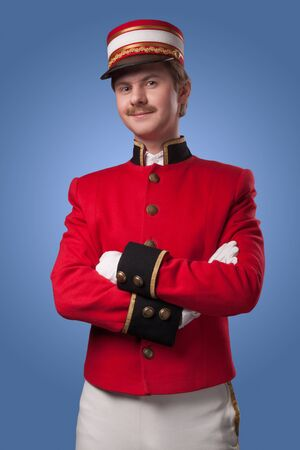 Portrait of a concierge  porter  in a red jacket on a blue background  photo