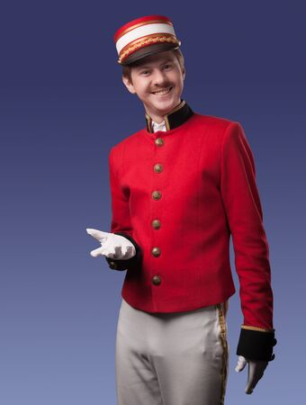 Portrait of a concierge  porter  in a red jacket on a blue background  Stock Photo