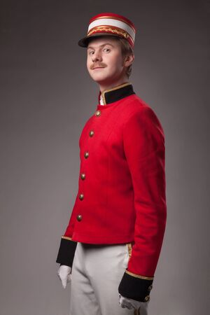 Portrait of a concierge  porter  in a red jacket on a gray background  photo