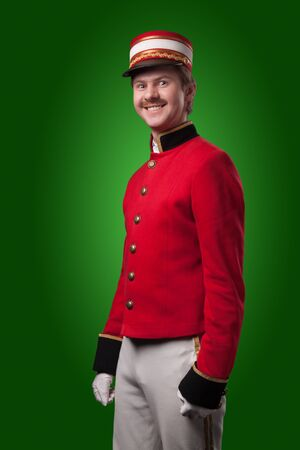 doorkeeper: Portrait of a concierge  porter  in a red jacket on a green background