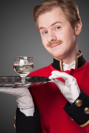 Smiling Waiter in red uniform with a tray with glasses on a grey background photo