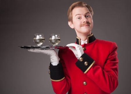 mixed age: Smiling Waiter in red uniform with a tray with glasses on a grey background