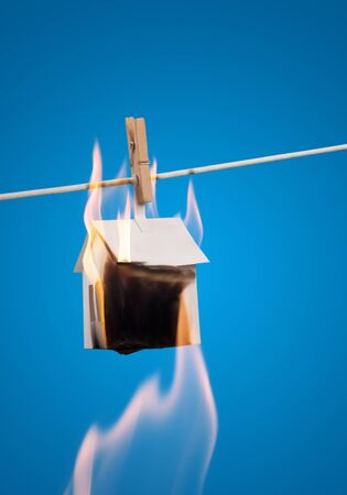 charred: Metaphor - fire  Burning paper house for clothespins on a rope