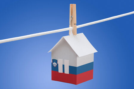 concept - Slovenia, Slovenian flag painted on a paper house hanging on a rope Stock Photo