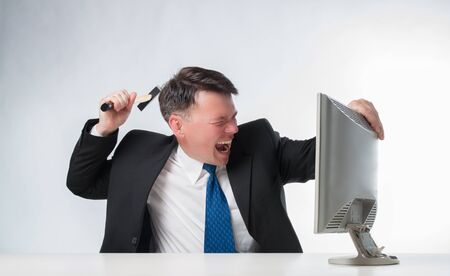 Angry businessman holding hammer over PC monitor photo