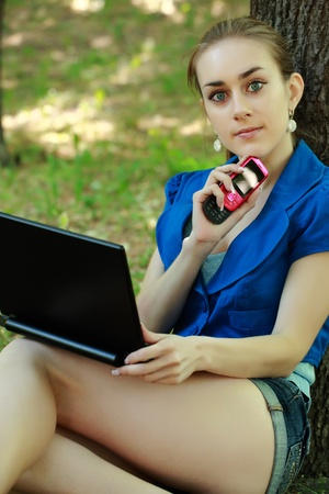 The young beautiful girl sits with the laptop in park near a tree in the summer photo