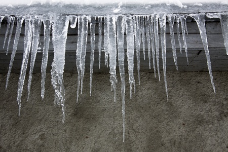 Icicles hang down from a roof in the winter largely In the winter
