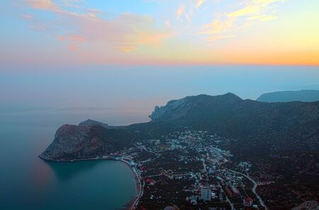 Coast with a small city, the top view on a sunset. A landscape photo