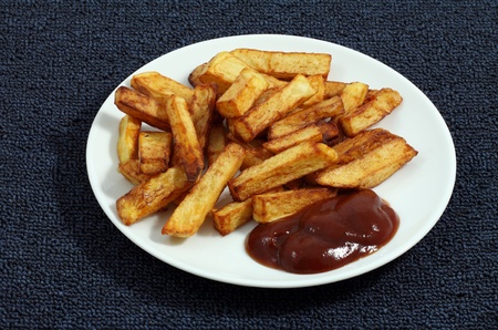 largely: Fried French fries with sauce largely on a white plate Stock Photo