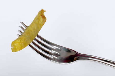 largely: Plug with the segment of a fried potato pinned on it largely on a white background with shades Stock Photo