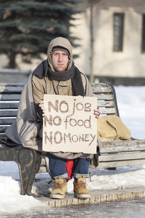 Young hungry homeless man with cardboard in winter city park