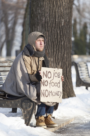 Young hungry homeless man in winter city park ask help