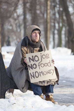 Young hungry homeless man in winter city park ask help by cardboard