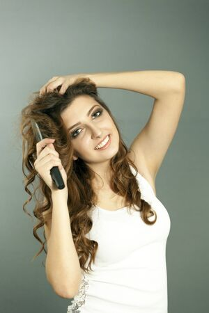 Attractive young girl with make-up hold hairbrush and smile