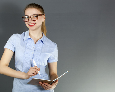 coquetry: Young smiling woman student with pen and notebook ready to write Stock Photo