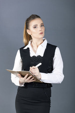 Young attractive business woman or secretary with pen and notebook looks directly.