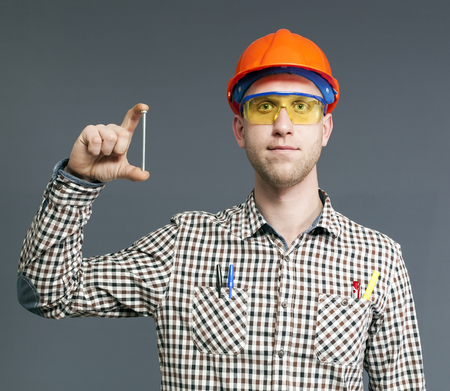 One long bolt in hand of satisfied young worker in helmet and glasses.
