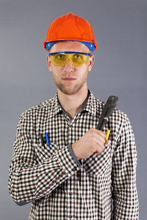 Plumber tool in hand of young worker in helmet and glasses.