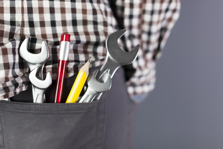 Wrenchs and toos, yellow pencil in hip pocket of trousers. Close up Symbol of work man