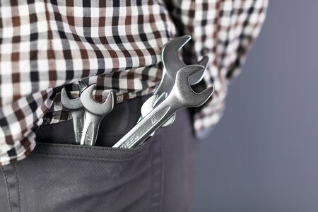 Wrenchs in hip pocket of trousers. Close up Symbol of work man Standard-Bild
