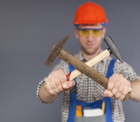 Vigorous young worker in uniform with two cross hammers in hands. Blurred figure
