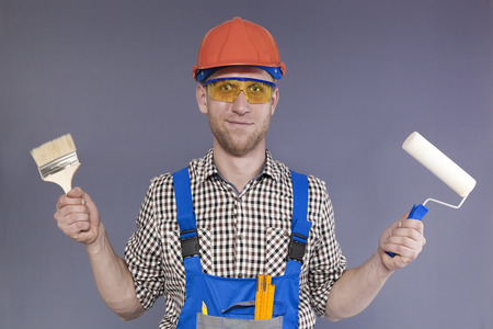 Happy modern young worker painter stand with brush and roller Standard-Bild
