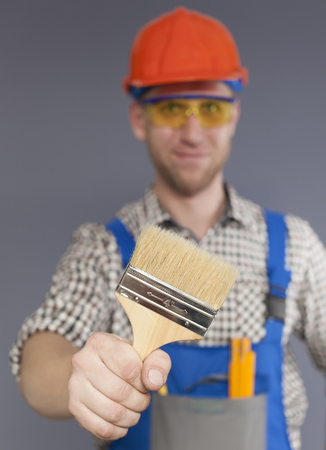 Paint brush and blurred figure of Happy modern young worker