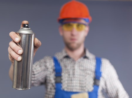 Cylinder with paint and blurred figure of Happy modern young worker