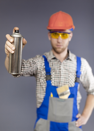 Cylinder with paint in front and blurred figure of modern young worker Standard-Bild
