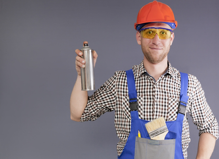 Cylinder with paint in front and modern smiling happy young worker