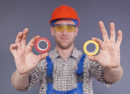 Insulating tapes in front and blurred smiling happy young worker Standard-Bild