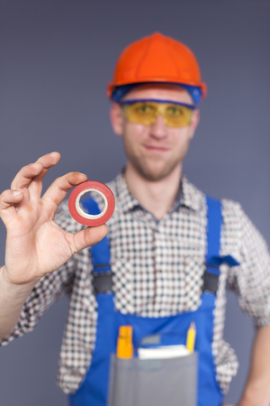 Red Insulating tape in front and blurred smiling happy young worker