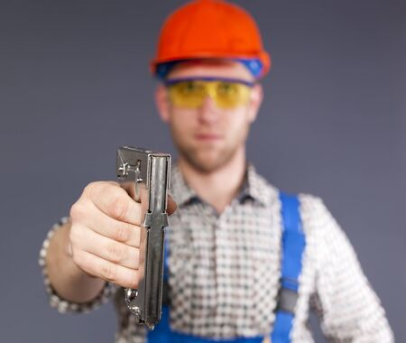 Industrial stapler and blurred figure of young worker