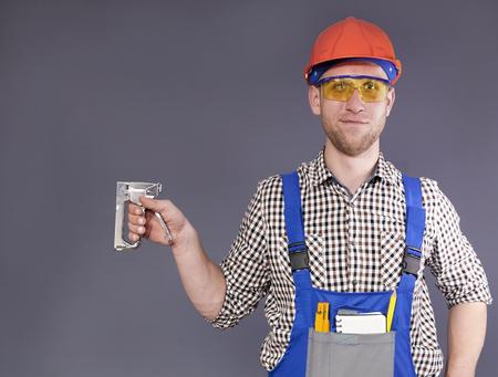 Industrial stapler and smiling happy young worker in uniform Standard-Bild