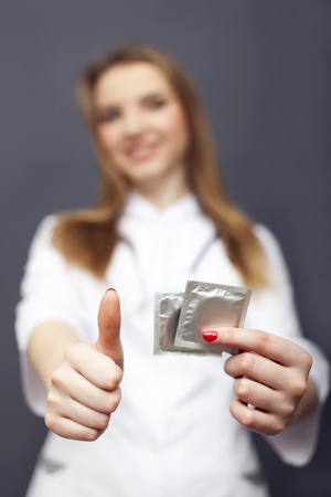 Young doctor, nurse for safe sex with condoms. Conceptual image for health life Standard-Bild