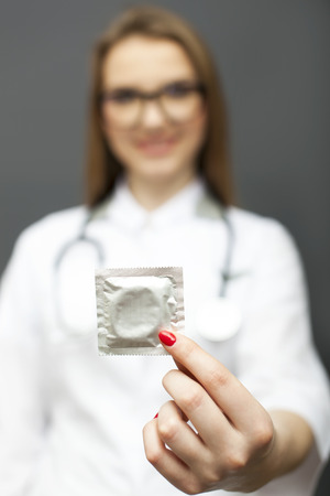Blurred figure of woman doctor, nurse in glasses with condom on palm. Conceptual image