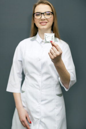 Blurred figure of smiling woman doctor in glasses with condom on palm. Conceptual image