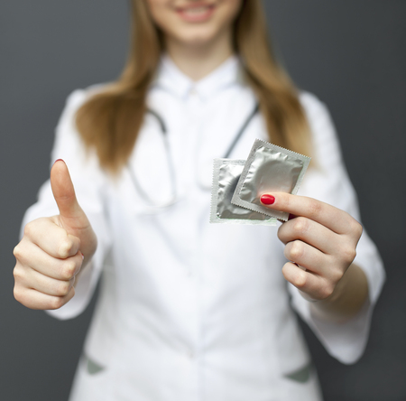 Smiling woman doctor, nurse with condom on palm and finger up. Cropped image