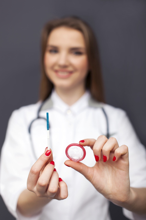 Attractive blurred woman doctor figure with condom on palm and pregnancy test Standard-Bild