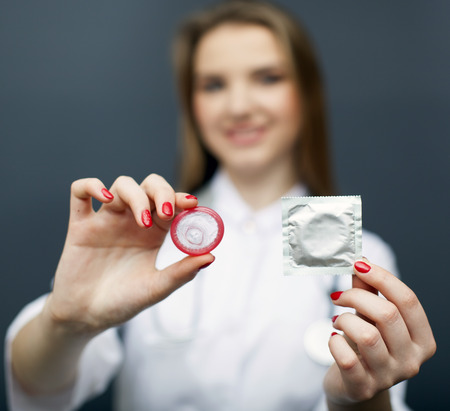Attractive blurred woman doctor figure with red condom on palm